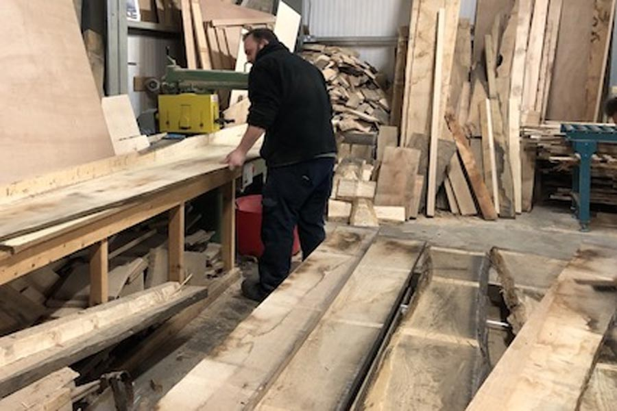 Cross cutting timber in workshop
