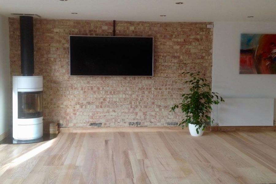 engineered ash sitting room floor with woodburner and brick feature wall