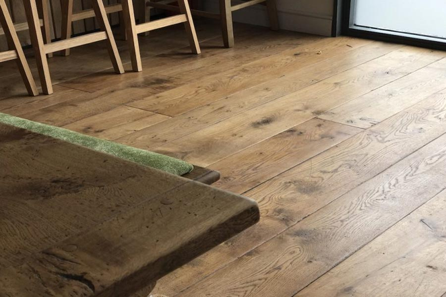 solid oak floorboards with corner wood table and stools